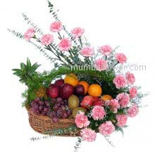 An arrangement of mixed fruits and pink carnations in a beautiful basket.