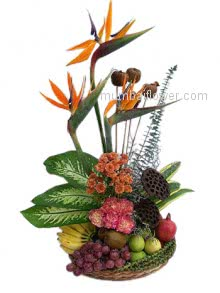 An arrangement with Birds of paradise, carnations and crysanthimums with fresh fruits.