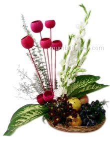 An arrangement of white gladioli and crysthimums with mixed fruits artistically decorated.