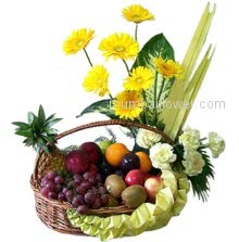 A fantastic arrangement of yellow gerberas and carnations with mixed fresh fruits in a beautiful basket.