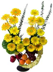 Arrangement of yellow gerberas with fresh fruits to your friend.