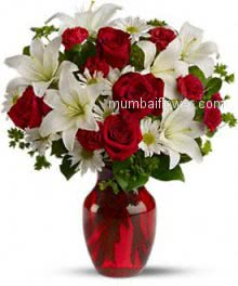 Beautiful arrangement of white lilies and Red roses in a clear glass vase. 20 Roses and 6 PC Lilies
