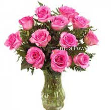 Glass vase with 12 Pink Roses nicely decorated with fillers and greens