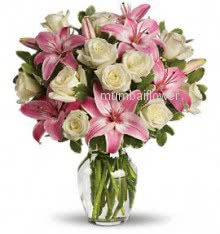 Glass vase with 5 stems of pink lilies and 15 White roses nicely decorated with  greens