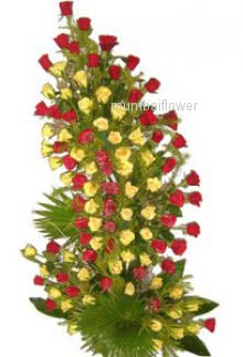 Tall Arrangement of 100 Red and Yellow Roses nicely decorated with greens