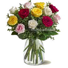 Glass vase with 15 mixed colored roses nicely decorated with greens