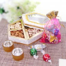 Hamper of Dryfruits in decorative box with potli of mixed chocolates and  Golden metalic color tealight holder. This Combo Contains 250gms of Mixed Dry Fruits,  8pc Small Chocolates and 2pc  Tealight Holder
