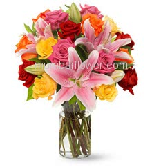 Glass Vase with mixed flowers lilies roses carnations with fillers greens